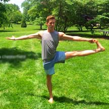 Alex Lehman in a yoga pose in a sunny field