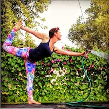 Ashley Rae Swanson in a yoga pose while watering flowers
