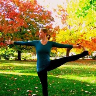 Colleen Taylor in a yoga pose in a field during autmn