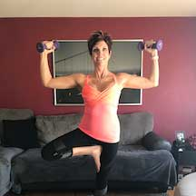 Denice Smith in a yoga pose, holding small dumbells