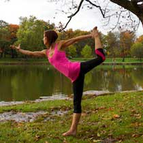 Fiona Jenkins in a yoga pose on the edge of a lake