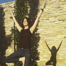 Jen Pope in a yoga pose in front of a stone wall