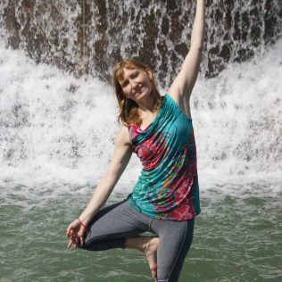 Jenni Antonicic in a yoga pose in front of a fountain