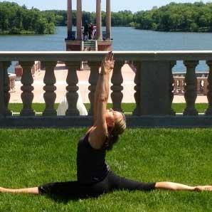 Lara Devine in a yoga pose in a grassy field near a lake
