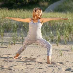 Loreta Medoniene in a yoga pose on a grassy beach