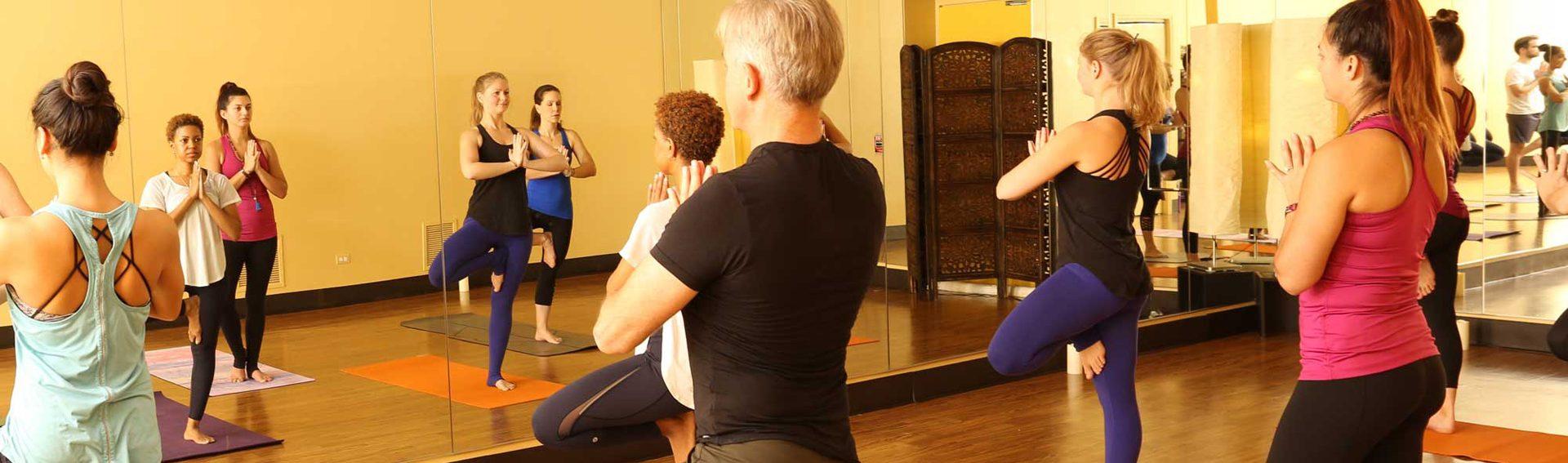 Yoga class, advanced pose involving balancing on one leg