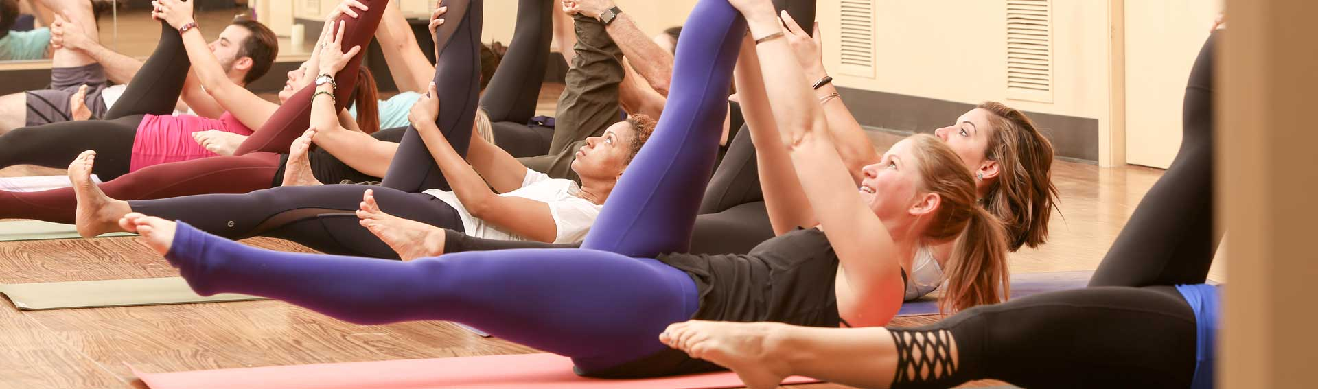 Yoga class participants lay on their backs with one leg in the air
