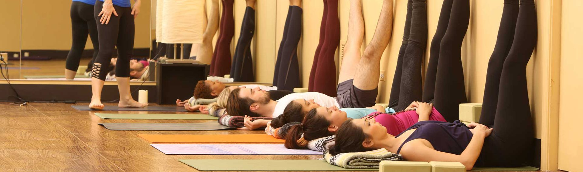 Yoga class, laying on their backs with their legs in the air against a wall