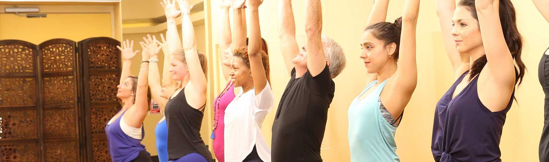 Yoga class standing with one leg forward and the other back, and their arms in the air
