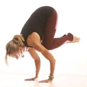 Woman in a yoga pose, balancing on her hands